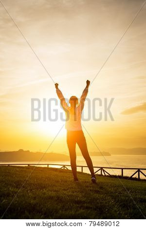 Happy Female Athlete Raising Arms Towards The Sun