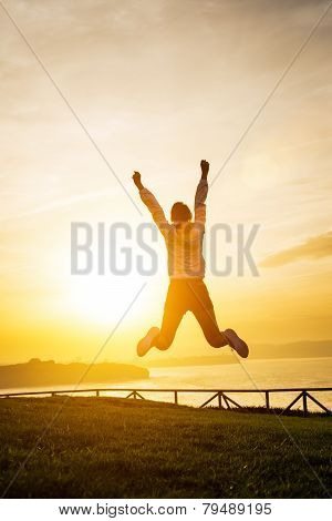 Happy Female Athlete Jumping Towards The Sun