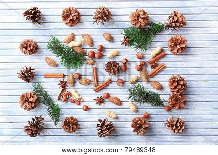 Sprigs of Christmas tree with bumps,  spices and nuts on color wooden background