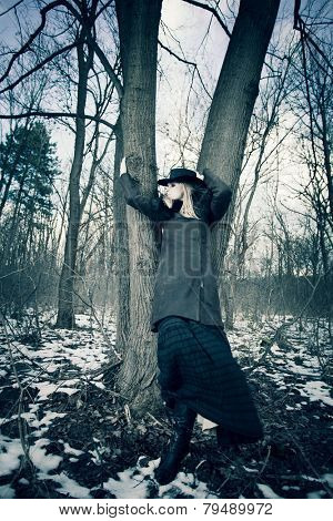 blonde woman wearing hat, leather coat and long skirt stand by tree  in the forest, cold winter day, full body shot