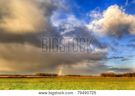 Landscape Of Grassland With Rainbow At The Horizon