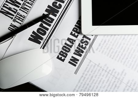 On-line news concept.Computer mouse, PC tablet and newspaper, close-up