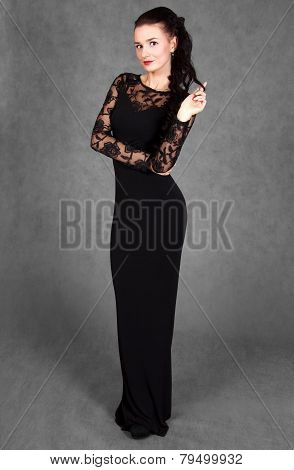Portrait Of A Young Attractive Woman In A Black Evening Dress