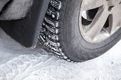 foto of stud  - Fragment of modern automotive wheel with studded tires and winter snowy road - JPG