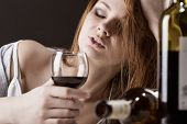 image of forlorn  - Young beautiful woman in depression drinking alcohol