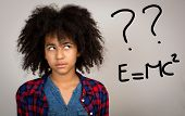 picture of wacky  - Young teenage girl with wacky afro hair looking up thinking and solving problems isolated against a grey background - JPG