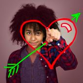 stock photo of wacky  - A mixed race teenage girl with afro hairstyle drawing a love heart with arrow in the air - JPG