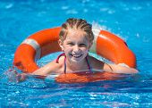 foto of lifeline  - smiling cute little girl swims with a lifeline in the pool in  summer - JPG