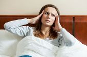 pic of dizziness  - Image of woman having migraine lying in bed - JPG