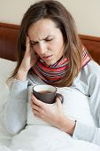 foto of high fever  - Lying woman in scarf having high fever - JPG