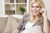 foto of settee  - A beautiful young woman talking on her cell phone at home - JPG