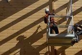 foto of labourers  - A painter uses an airless spray to apply timber preservative to an industrial wooden building - JPG