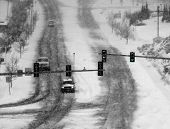 stock photo of storms  - Snowy winter road with cars driving on roadway in snow storm and traffic lights - JPG