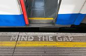 picture of gap  - Closeup of mind the gap sign on a platform edge with open train door - JPG
