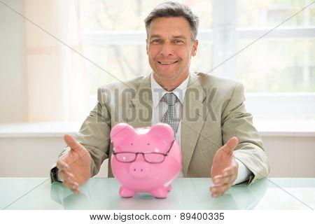 Happy Businessman With Piggybank On Desk