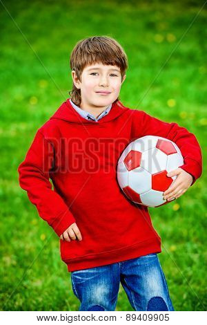 Cute 7 years old boy playing with a ball outdoor. Summer day.