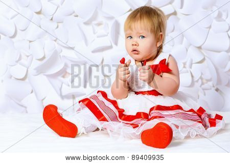 Cute baby girl in a beautiful dress on a background of white paper flowers. Childhood. Baby fashion.