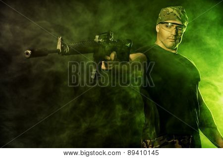 Courageous soldier in camouflage holding automatic rifle. Military.