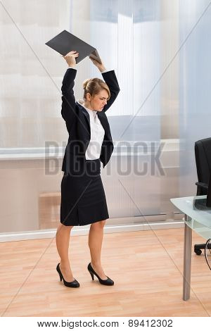 Businesswoman In Rage Throwing Laptop
