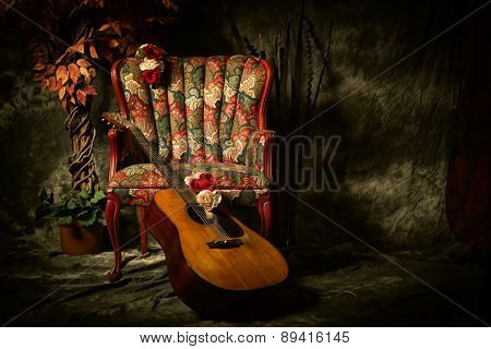 Vintage Acoustic Guitar Leaning Against Antique Chair