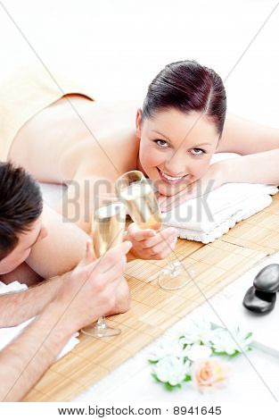 Caucasian Young Couple Lying On A Massage Table And Drinking Champagne
