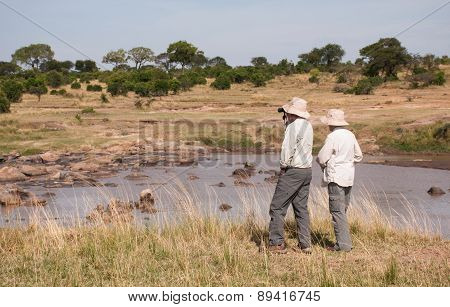 Safari in Tanzania, tourists with binoculars looking at the view over the Mara River