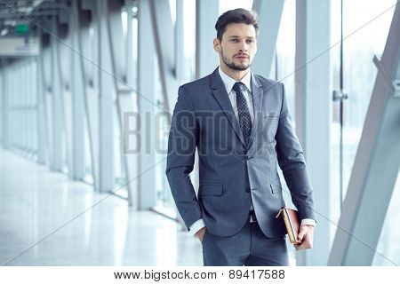 Portrait of a  young businessman in suit standing at office