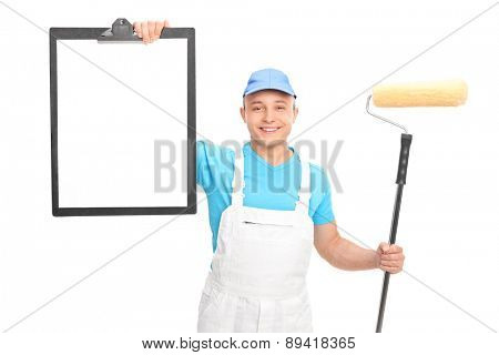 Young male painter in a white uniform holding a paint roller and showing a clipboard with a blank paper on it isolated on white background