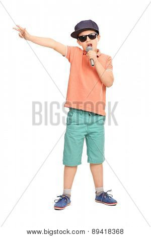 Full length portrait of a little boy in hip hop outfit rapping on a microphone and gesturing with his hand isolated on white background