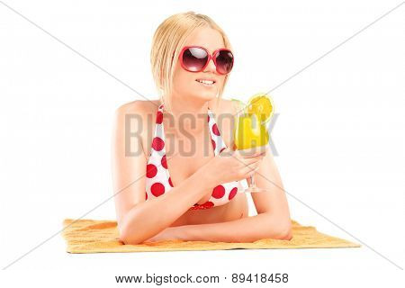 Relaxed blond woman in bikini lying on a towel and holding an orange cocktail isolated on white background