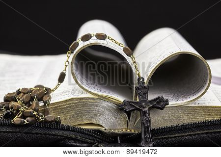 Bible Folded With Vintage Rosary on Black Background