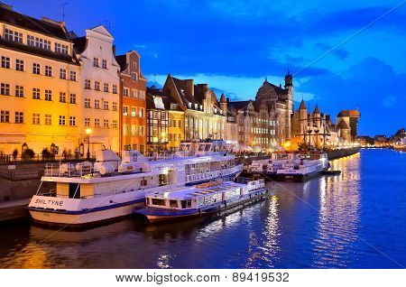 Tourist boats and colourful historic houses at night in Gdansk, Poland.