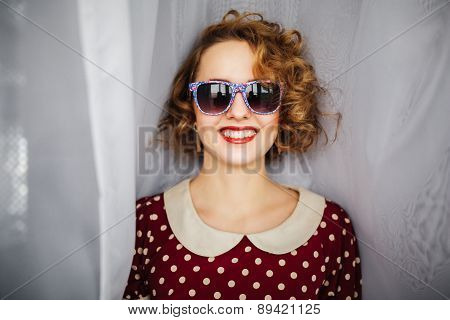 girl with curly short hair red lips in retro glasses