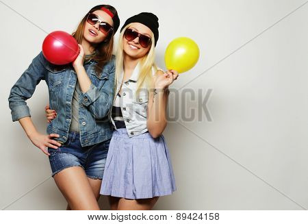 Two happy hipster girls smiling and holding colored balloons over white background