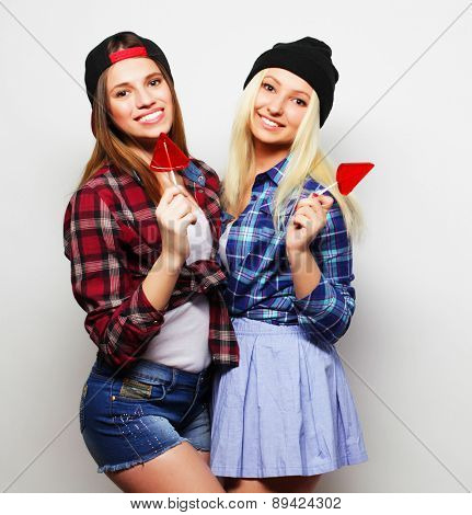 portrait of two young pretty hipster girls wearing hats and sunglasses holding candys. Studio portrait of two cheerful best friends having fun and making funny faces.