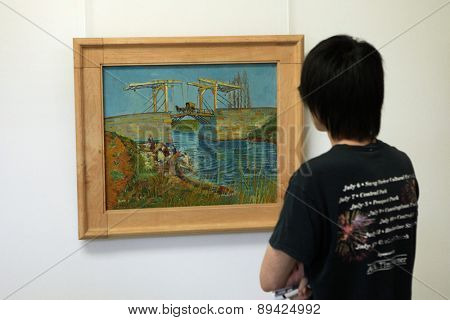 OTTERLO, NETHERLANDS - AUGUST 8, 2012: Visitor looks at the painting The Langlois Bridge at Arles (1888) by Vincent van Gogh in the Kroller Muller Museum in Otterlo, Netherlands.