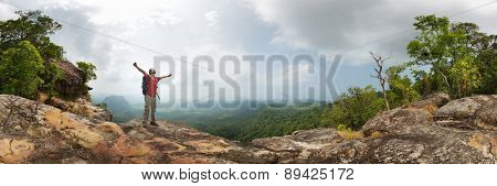 Hiker with backpack standing on top of the mountain with raised hands