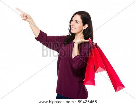 Brunette woman hold with shopping bag and finger point up