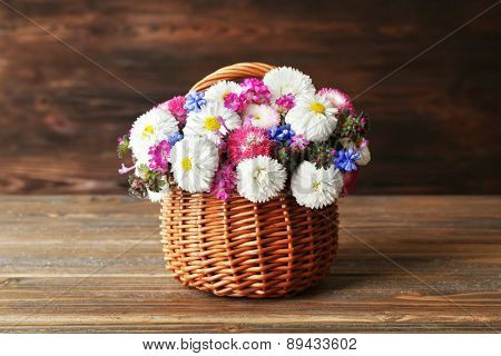 Beautiful colorful daisy in wicker basket on wooden background