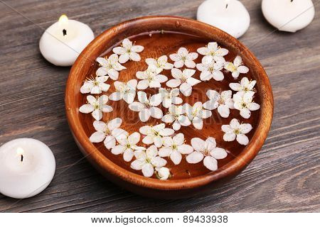 Spa still life with petals and candlelight on wooden background