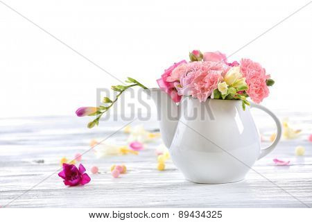Beautiful spring flowers in teapot isolated on white