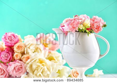 Composition beautiful spring flowers in teapot on light blue background