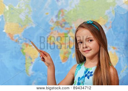 Little student girl pointing to blurry world map with pencil - copy space