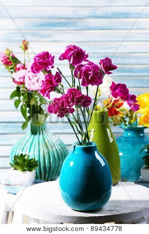 Different beautiful flowers in vases on wooden background