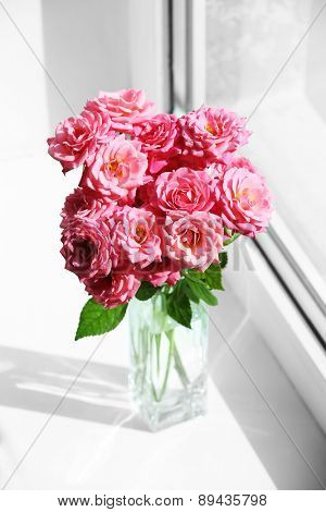 Bouquet of beautiful fresh roses on windowsill background