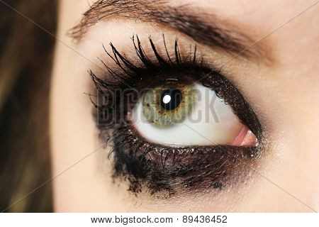 Eye of young woman with tear drop close up