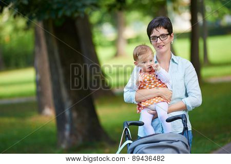 portrait of happy mom and baby daughter smiling at park nature