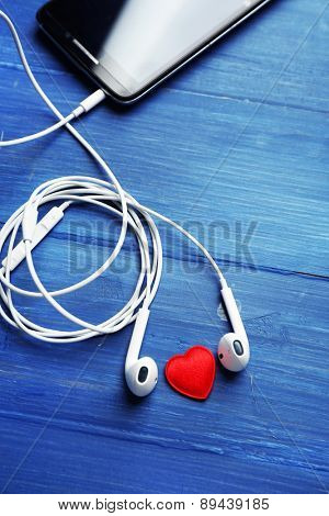 Mobile phone and earphones on color wooden background
