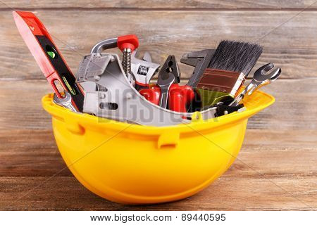 Construction tools in helmet on wooden background