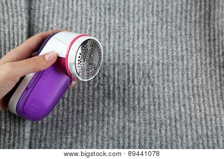 Female hands with Wool shaver on wool sweater background